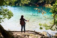 Punto di vista posteriore della donna turistica con lo zaino che sta sulla riva del lago che prende immagine fotografia stock