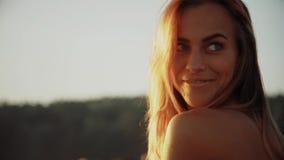 Punto di vista posteriore della giovane donna alla spiaggia che si rilassa dal mare di estate stock footage