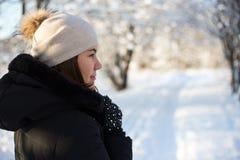 Punto di vista posteriore della giovane donna che cammina nella foresta di inverno Fotografia Stock