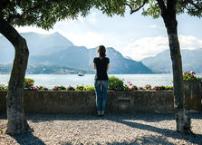 Punto di vista posteriore della giovane donna che si rilassa sulla banchina del lago Como della montagna immagine stock libera da diritti