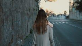 Punto di vista posteriore della giovane signora che cammina nel centro urbano da solo Femmina con capelli lunghi che vanno vicino stock footage