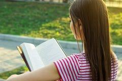 Punto di vista posteriore della ragazza adorabile con bei capelli lunghi che legge un libro fuori Fotografia Stock