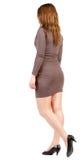 Punto di vista posteriore della ragazza andante in vestito marrone. Immagini Stock