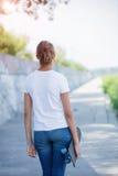 Punto di vista posteriore della ragazza che porta maglietta bianca in bianco, jeans che posano contro la parete ruvida della via Immagini Stock Libere da Diritti
