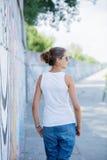 Punto di vista posteriore della ragazza che porta maglietta bianca in bianco, jeans che posano contro la parete ruvida della via Fotografie Stock Libere da Diritti