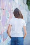 Punto di vista posteriore della ragazza che porta maglietta bianca in bianco, jeans che posano contro la parete ruvida della via Fotografia Stock Libera da Diritti