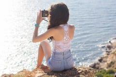 Punto di vista posteriore della ragazza del fotografo che fa le immagini dalla vecchia macchina fotografica Immagini Stock