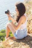 Punto di vista posteriore della ragazza del fotografo che fa le immagini dalla vecchia macchina fotografica Fotografia Stock
