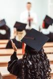 punto di vista posteriore della ragazza dello studente in mani d'applauso del cappello di graduazione mentre sedendosi Fotografia Stock