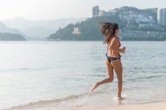 Punto di vista posteriore della ragazza esile di misura che corre a piedi nudi sul bikini d'uso della spiaggia Giovane donna che  immagini stock libere da diritti