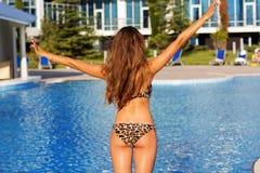 Punto di vista posteriore della ragazza nella piscina con acqua blu fotografia stock