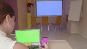 Punto di vista posteriore della ragazza di seduta che esamina lo schermo del computer portatile e dello smartphone che si prepara stock footage