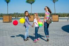 Punto di vista posteriore delle scolare dei bambini che si tengono per mano insieme passeggiata sul fondo urbano della strada all Fotografia Stock Libera da Diritti