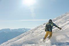 Punto di vista posteriore dello snowboarder maschio di freeride che fa scorrere giù la collina nevosa immagini stock libere da diritti