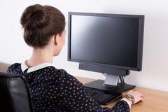 Punto di vista posteriore di bella donna di affari in ufficio facendo uso del computer w Fotografia Stock