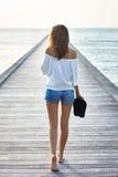 Punto di vista posteriore di giovane bella donna che cammina sul pilastro fotografia stock libera da diritti