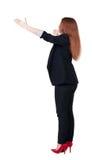 Punto di vista posteriore di giovane donna di affari della testarossa che indica a wal Fotografie Stock Libere da Diritti