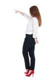 Punto di vista posteriore di giovane donna di affari della testarossa che indica a wal Fotografia Stock