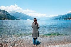 Punto di vista posteriore di giovane donna sola che si rilassa sul lago Como in Italia immagine stock