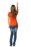 Punto di vista posteriore di giovane femmina casuale nell'indicare integrale allo spazio in bianco della copia Immagini Stock