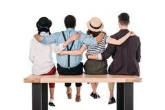 Punto di vista posteriore di giovani amici alla moda che si siedono abbraccio sul banco Fotografia Stock