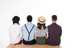 Punto di vista posteriore di giovani amici alla moda che si siedono insieme sul banco di legno Fotografie Stock