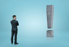 Punto di vista posteriore di un uomo d'affari che esamina grande punto esclamativo concreto 3D isolato su fondo blu Fotografie Stock Libere da Diritti