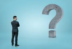 Punto di vista posteriore di un uomo d'affari che esamina il grande punto interrogativo concreto 3D isolato su fondo blu Fotografia Stock Libera da Diritti