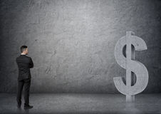 Punto di vista posteriore di un uomo d'affari che esamina il grande simbolo di dollaro del calcestruzzo 3D Fotografia Stock Libera da Diritti