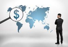Punto di vista posteriore di un uomo d'affari che esamina la mappa di mondo con il simbolo di dollaro d'ingrandimento della grand Fotografie Stock