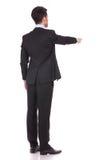 Punto di vista posteriore di un uomo d'affari che indica dito Immagine Stock