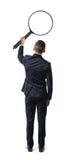 Punto di vista posteriore di un uomo d'affari che tiene grande lente d'ingrandimento in suo braccio steso isolato su fondo bianco Immagine Stock