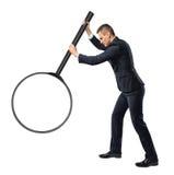 Punto di vista posteriore di un uomo d'affari che tiene grande lente d'ingrandimento in suo braccio steso isolato su fondo bianco Fotografia Stock Libera da Diritti
