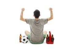 Punto di vista posteriore di un uomo emozionante con pallone da calcio e pacchetto di birra che esamina parete Isolato su bianco Fotografia Stock Libera da Diritti