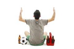 Punto di vista posteriore di un uomo emozionante con pallone da calcio e pacchetto di birra che esamina parete Isolato su bianco Fotografie Stock