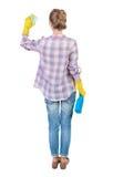 Punto di vista posteriore di una casalinga in guanti con la spugna ed il detersivo Fotografia Stock