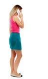 Punto di vista posteriore di una donna che parla sul telefono Fotografia Stock