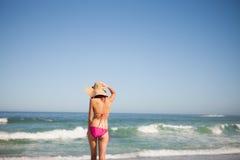 Punto di vista posteriore di una giovane donna in beachwear che sta davanti al fotografie stock libere da diritti