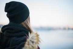 Punto di vista posteriore di una ragazza triste contro il backgroun vago di inverno Fotografia Stock