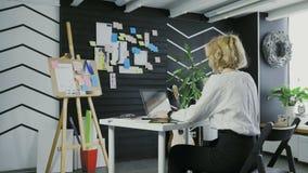 Punto di vista posteriore di giovane donna di affari che lavora al computer nell'ufficio archivi video