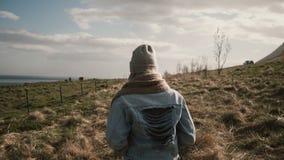 Punto di vista posteriore di giovane donna alla moda che cammina attraverso il campo vicino al fiume Femmina nel ranch dei cavall Immagini Stock Libere da Diritti