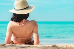 Punto di vista posteriore di giovane donna asiatica felice in cappello rosa di paglia e del costume da bagno rilassarsi e godere  fotografia stock