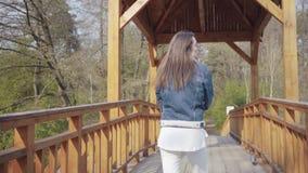 Punto di vista posteriore di giovane donna di fascino che cammina lentamente sul ponte di legno che guarda intorno Ammirare della video d archivio