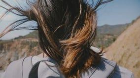 Punto di vista posteriore di giovane donna turistica con capelli che volano in forte vento che guarda paesaggio epico al ponte de archivi video