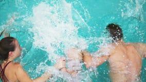 Punto di vista posteriore di giovani madre e padre insieme al loro bambino che salta nel tenersi per mano della piscina Madre e archivi video