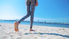 Punto di vista posteriore inferiore di bella giovane donna atletica esile in leggins che cammina sulla spiaggia di sabbia alla ma archivi video
