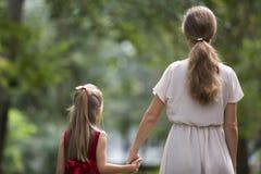 Punto di vista posteriore di piccola ragazza dai capelli lunghi bionda del bambino con la madre esile snella in vestiti alla moda immagini stock libere da diritti