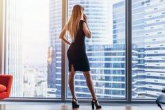 Punto di vista posteriore di riuscita donna di affari che ha conversazione telefonica che guarda fuori la finestra con la vista d fotografia stock libera da diritti