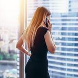 Punto di vista posteriore di riuscita donna di affari che ha conversazione telefonica che guarda fuori la finestra con la vista d fotografia stock