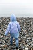 Punto di vista posteriore di un bambino corrente al mare in un impermeabile e negli stivali di gomma Fuoco selettivo fotografia stock libera da diritti